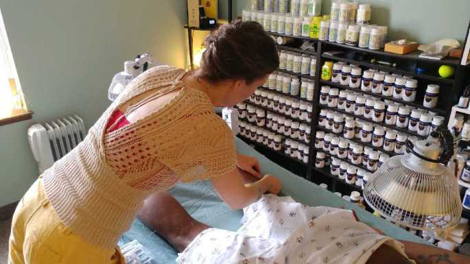 Kat performing acupuncture with Chinese herbs in background